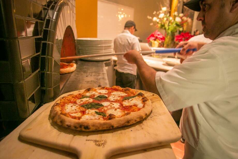 Paul Aguirre puts a pizza into the oven with a Margherita pizza in the foreground. (Special to the Chronicle)