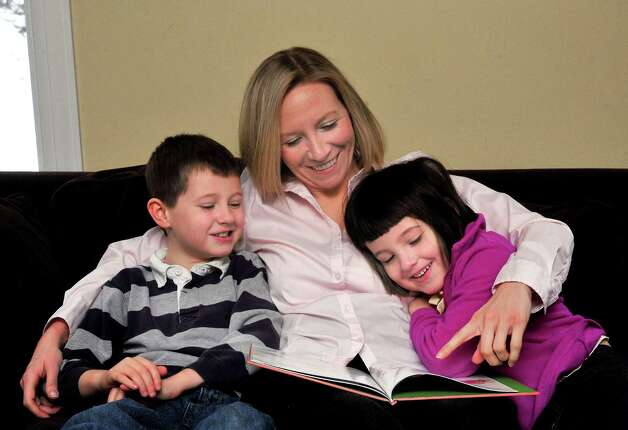 Patty Lennon, who has a multimedia company called Mom Gets a Life, reads with her children, Matthew, 7, and Katie, 5, in their Danbury home Thursday, Dec. 27, 2012. Photo: Michael Duffy / The News-Times