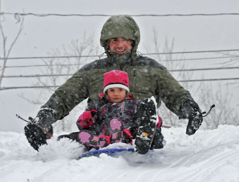 Joe Mangiaracina of Voorheesville and his daughter Carly, 4, enjoy sledding on the hill at the Tawasentha Park Winter Recreation Area during the Capital Region's first snow storm of the season on Thursday Dec. 27, 2012 in Guilderland, N.Y. (Lori Van Buren / Times Union) Photo: Lori Van Buren