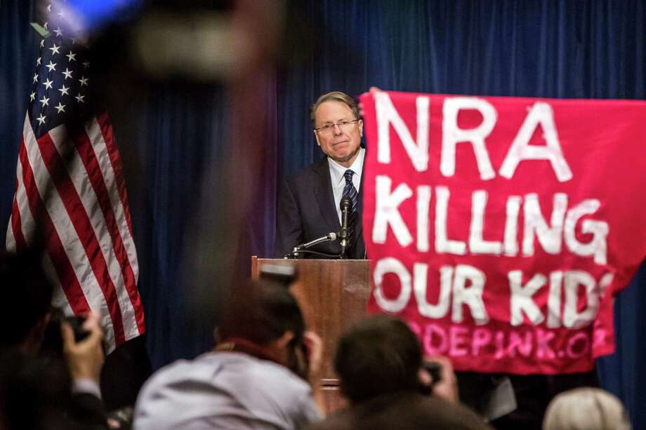 An activist with Code Pink interrupts Wayne LaPierre, executive vice president of the National Rifle Association, during a news conference held to address the Newtown, Conn., mass shooting, in Washington, Dec. 21, 2012. During the news conference Friday, the NRA called for armed protection for each school in the country as the best way to protect children from gun violence. Photo: BRENDAN HOFFMAN, New York Times / NYTNS