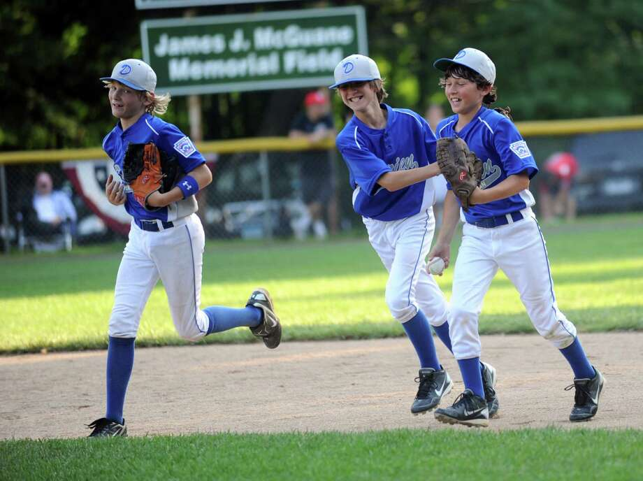 Justin Van de Graaf, right, is congratulated by Darien teammate Fin Batson, center, after Van de Graaf made a diving catch during Friday's Little League game against Stamford at McGuane Field in Darien on June 29, 2012. Photo: Lindsay Niegelberg / Stamford Advocate