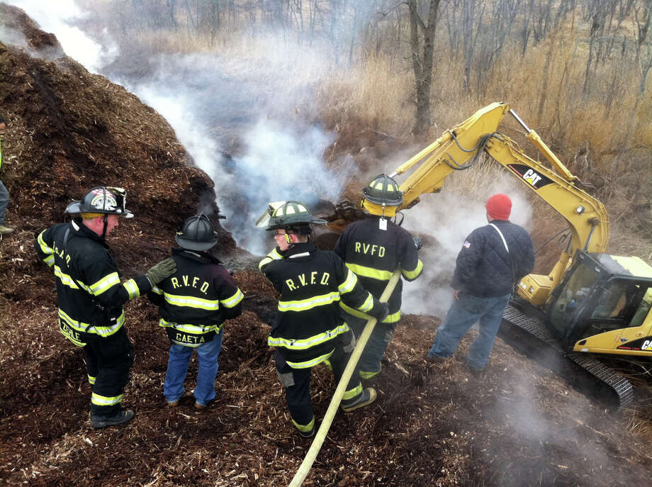 Members of the Ridgefield Fire Department battle a stubborn fire that erupted in a giant wood chip pile near the Town Transfer Station on South Street. By Thursday the fire in the pile was out, but it took firefighters nearly a week to subdue the smoldering blaze. Photo: Contributed Photo/ Ridgefield Fi, Contributed Photo / The News-Times Contributed