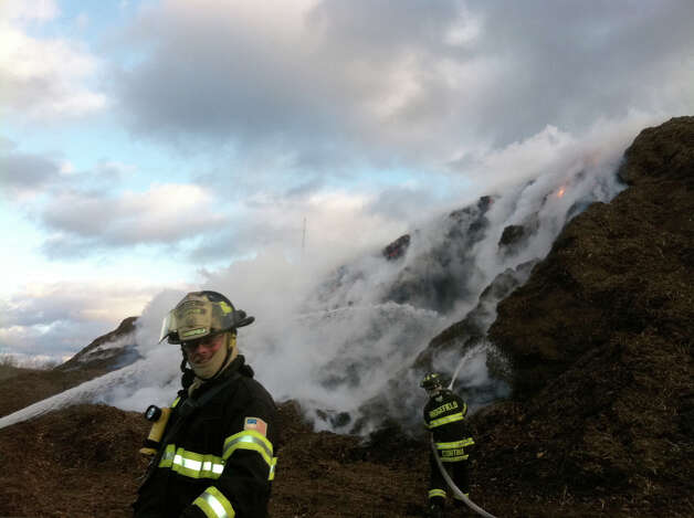 Members of the Ridgefield Fire Department battle a stubborn fire that erupted in a giant wood chip pile near the Town Transfer Station on South Street. By Thursday the fire in the pile was out, but it took firefighters nearly a week to subdue the smoldering blaze. Photo: Contributed Photo / The News-Times Contributed