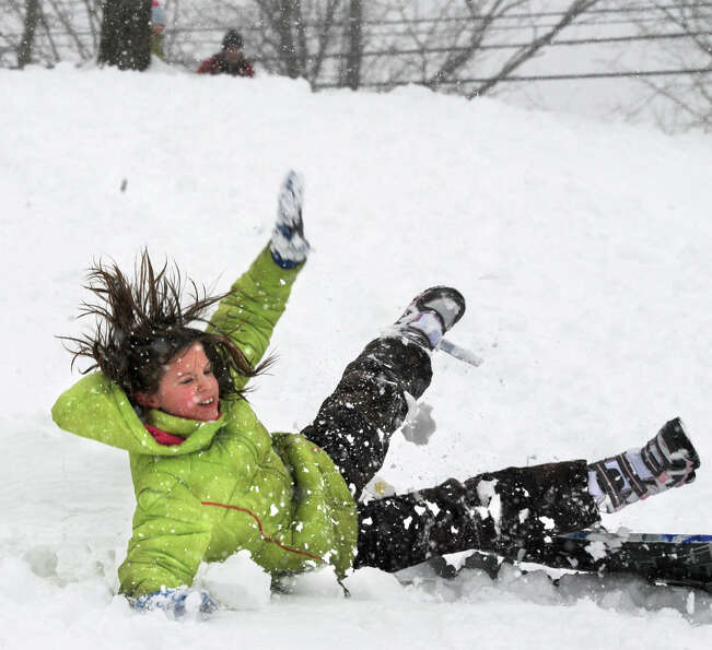 Lauren Buess, 9, falls off her sled as she goes over a jump on the hill at the Tawasentha Park Winte