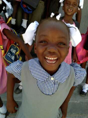 A little girl smiles after she receives new shoes from soles4souls in Fond Parisien, Haiti. Photo: Contributed