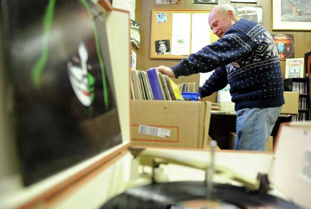 Ron Knox flips through a collection of records, a big seller for him, at Books By the Falls in Derby, Conn. The shop, Derby's only bookstore, opened in 1981 and sells books, antiques, art and records. Photo: Autumn Driscoll / Connecticut Post