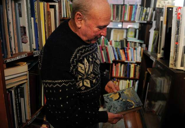 Ron Knox pulls out an older novel from his collection of  nearly 50,000 books dating back to the 1600s at Books By the Falls in Derby, Conn. The shop, Derby's only bookstore, opened in 1981 and sells books, antiques, art and records. Photo: Autumn Driscoll / Connecticut Post
