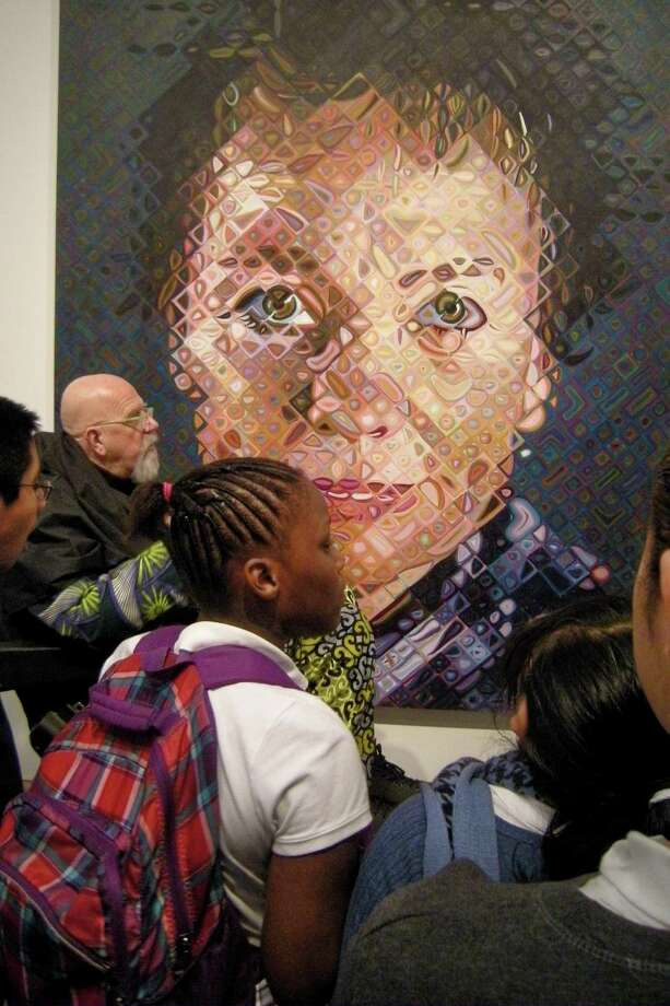 "International artist Chuck Close last week chats about one of his oil-on-canvas paintings (""Laurie,"" 2011) at Manhattan's Pace Gallery with students from Bridgeport's Roosevelt School. Photo: Phyllis A.S. Boros/Staff Photo"