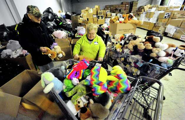 "Volunteers, including Cheryl Ghent, center, sort donations in the ""teddy bear room"" of a Simms Lane warehouse in Newtown Thursday, Dec. 27, 2012. Photo: Michael Duffy / The News-Times"