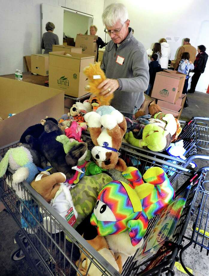 Volunteers, including Frank Gardner, sort donated stuffed animals in a Simms Lane warehouse in Newtown Thursday, Dec. 27, 2012. Photo: Michael Duffy / The News-Times