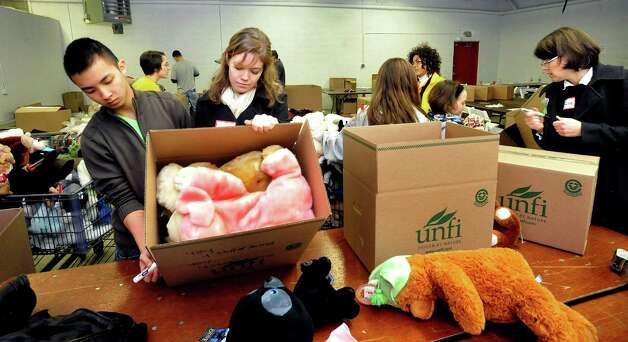 Volunteers, including Michael Savdo, 16, and Celina Weigel, 15, pack donated stuffed animals in a Simms Lane warehouse in Newtown Thursday, Dec. 27, 2012. Photo: Michael Duffy / The News-Times