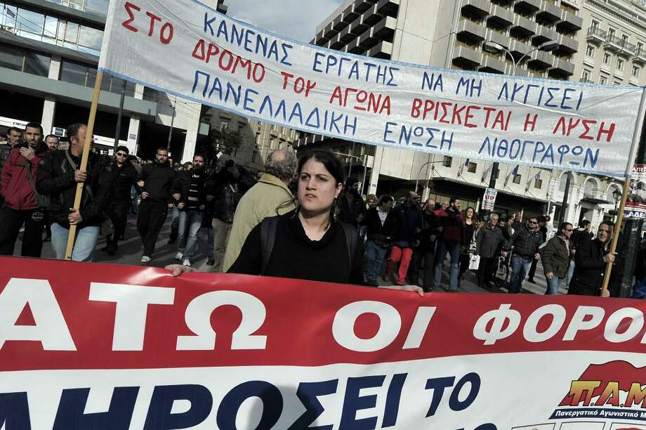 Protesters march towards the Greek parliament  in Athens on December 19, 2012 as Public services in Greece are hit by a 24-hour strike called by unions in protest at damage to the sector caused by sweeping austerity measures. The European Central Bank said today that it will begin accepting Greek bonds as collateral for central bank loans again, at a discount, a move that will give a boost to eurozone banks still holding the risky instruments.. AFP PHOTO / LOUISA GOULIAMAKILOUISA GOULIAMAKI/AFP/Getty Images Photo: LOUISA GOULIAMAKI, AFP/Getty Images / AFP