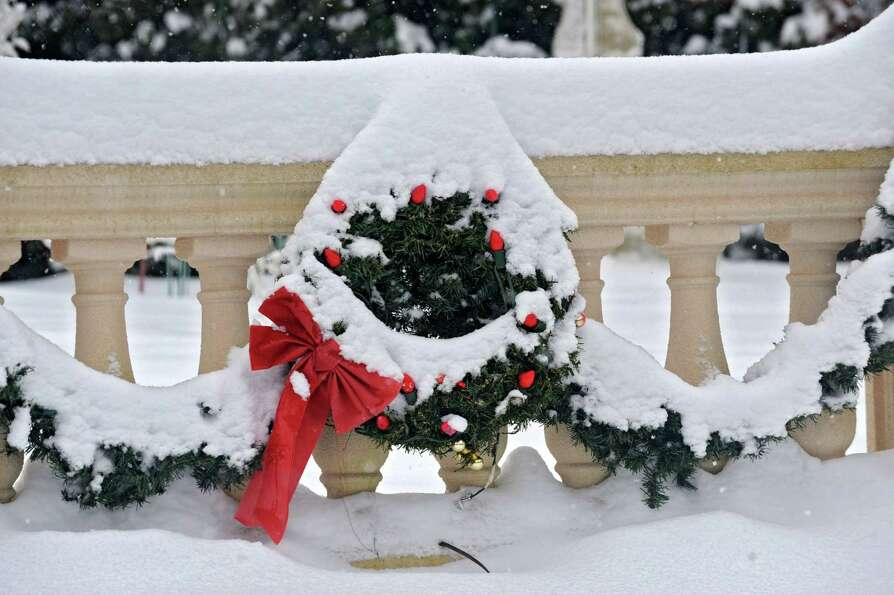 Snow covers a wreath decorated with a bow and lights during the Capital Region's first snow storm of