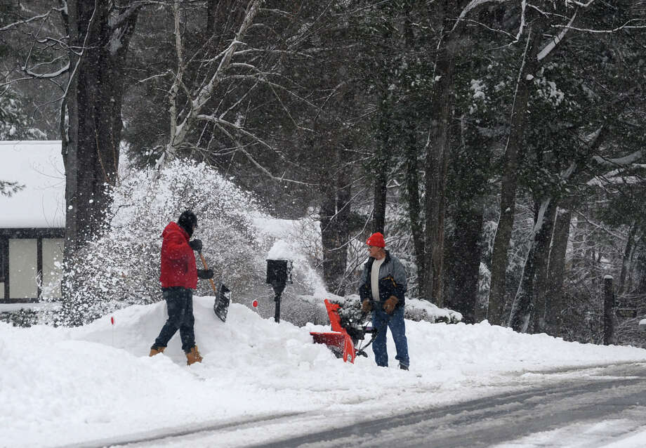 A couple neighbors use different tools to clear their driveways during the Capital Region's first snow storm of the season on Thursday Dec. 27, 2012 in Guilderland, N.Y. (Lori Van Buren / Times Union) Photo: Lori Van Buren