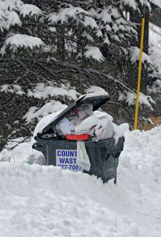 Trash cans were buried in deep snow at curbs during the Capital Region's first snow storm of the season on Thursday Dec. 27, 2012 in Guilderland, N.Y. (Lori Van Buren / Times Union) Photo: Lori Van Buren