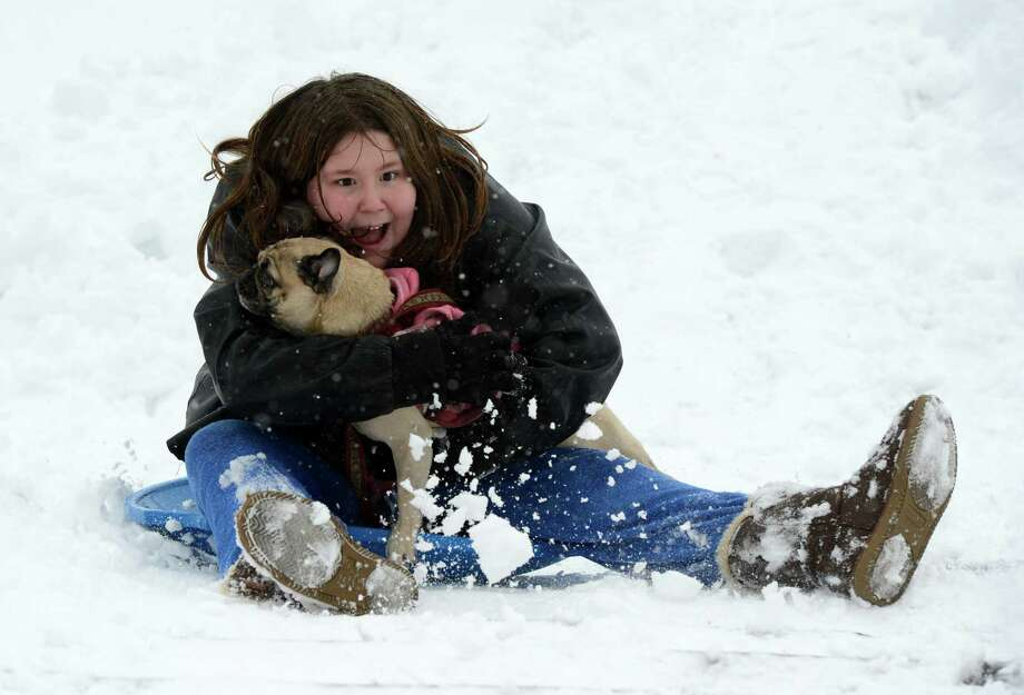 Shyanna Foster, 11, gives her pooch Miss Lita a fun ride as she slid down a hill in Lincoln Park in Albany, N.Y. Dec 27, 2012. (Skip Dickstein/Times Union) Photo: SKIP DICKSTEIN