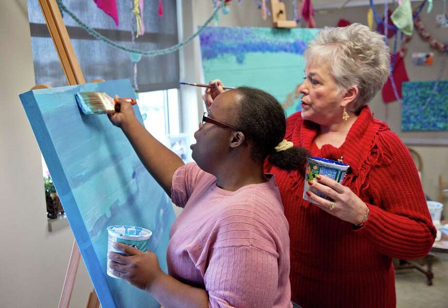 Volunteer Connie Harmon monitors Chanta Burton on her painting at the Melody McDowell Arty Center , located at the Texana Center in Rosenberg, Texas. Photo: Thomas B. Shea, For The Chronicle / © 2012 Thomas B. Shea