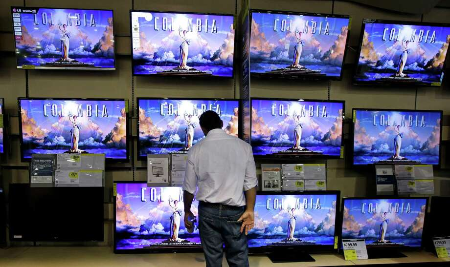 A shopper looks at televisions at a Best Buy store on Friday, Nov. 23, 2012, in Franklin, Tenn., after the store opened at midnight.  Black Friday got off to its earliest start ever as some of the nation's stores opened Thursday night, beating the traditional Friday opening. (AP Photo/Mark Humphrey) Photo: Mark Humphrey, Associated Press / AP