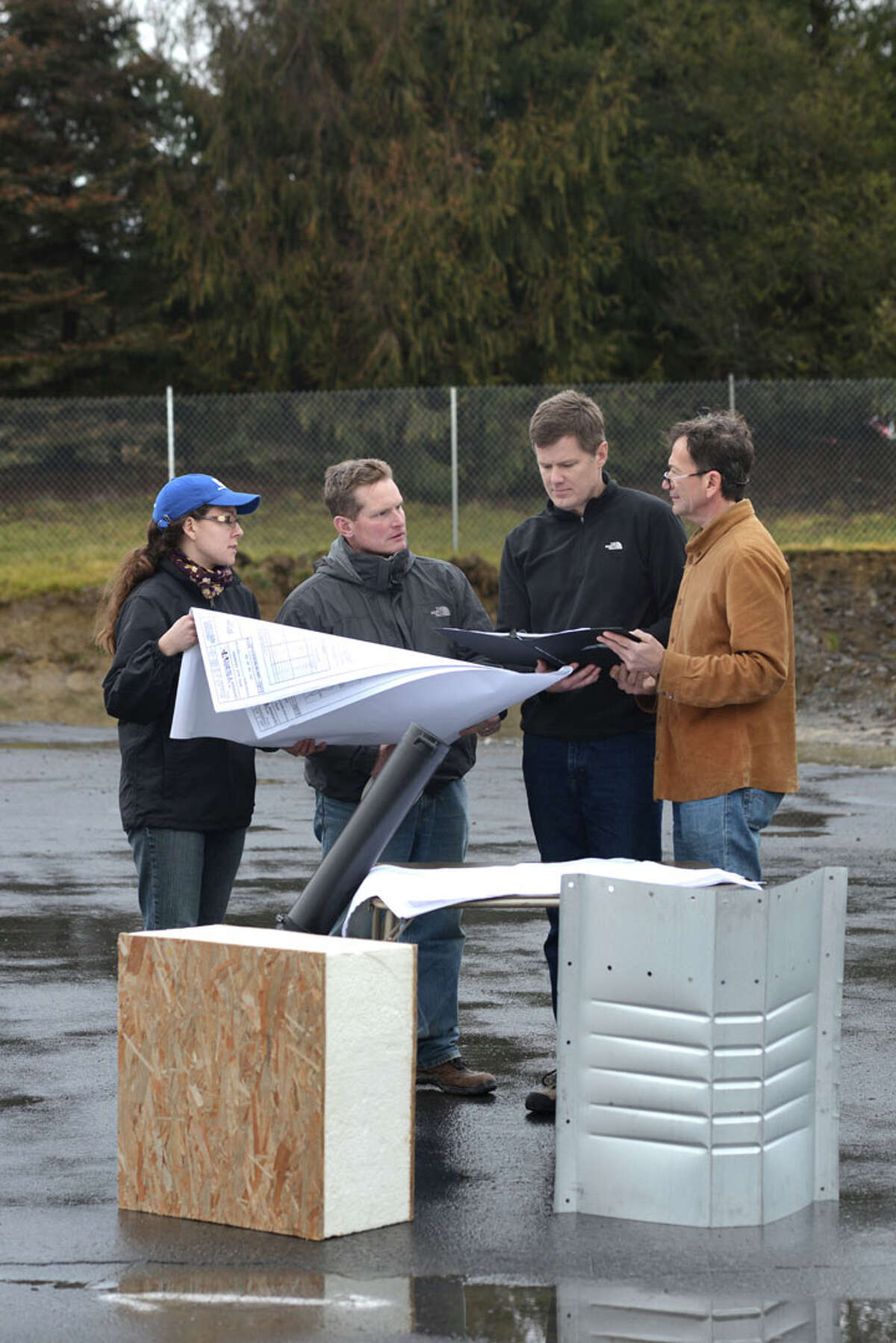 Hudson-based architect Dennis Wedlick, far right, reviews plans for a new passive office for TCI, an electrical transformer recycling company in Ghent, Columbia County. Wedlick desiged the first building in state to be certified under energy-efficient passive building standards.