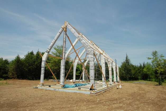 "The newly positioned frame for the Hudson Passive Project home is pictured with on Friday, June 25 2010.  The Dennis Wedlick Architect, LLC firm has designed the prototype for the house to be passively energy efficient by using heavy insulation and a ""magic box"", which allows fresh air to circulate in, while forcing stale air out to transfer heat and coolness.  This regulates the temperature within the house at all times of the year without any reliance on solar, geothermal, or wind turbine power. (Kayla Galway / Times Union) Photo: Kayla Galway / 00008923A"