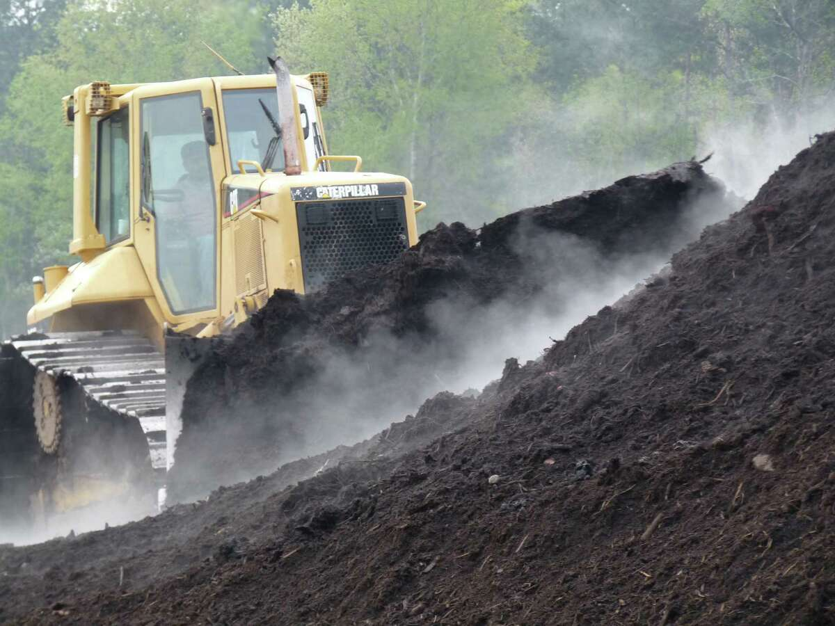 A bulldozer turns a commercial compost pile. High temperatures in the pile kill pathogens and weed seeds.