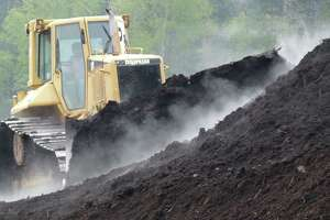 Bull-dozer turns a compost pile. Heat in the pile will reach 170 degree F, killing pathogens and weed seeds.