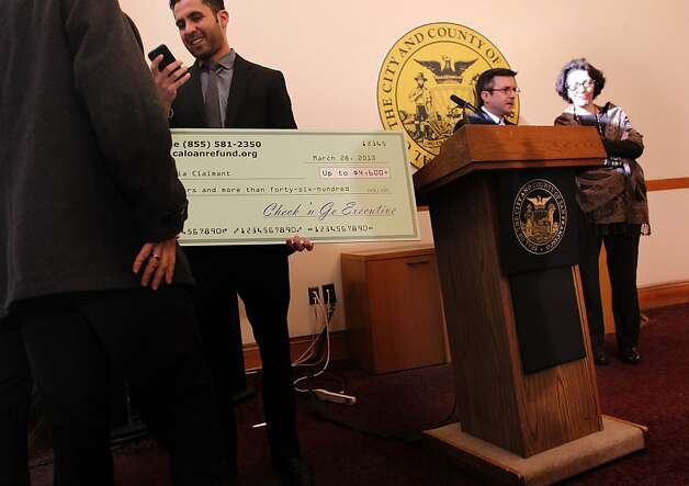 Marco Chavarin of the San Francisco treasurer and tax collector's office holds the oversize check symbolizing the $4.3 million settlement from Check 'n Go, which agreed to pay refunds to customers. Photo: Michael Macor, The Chronicle / SF
