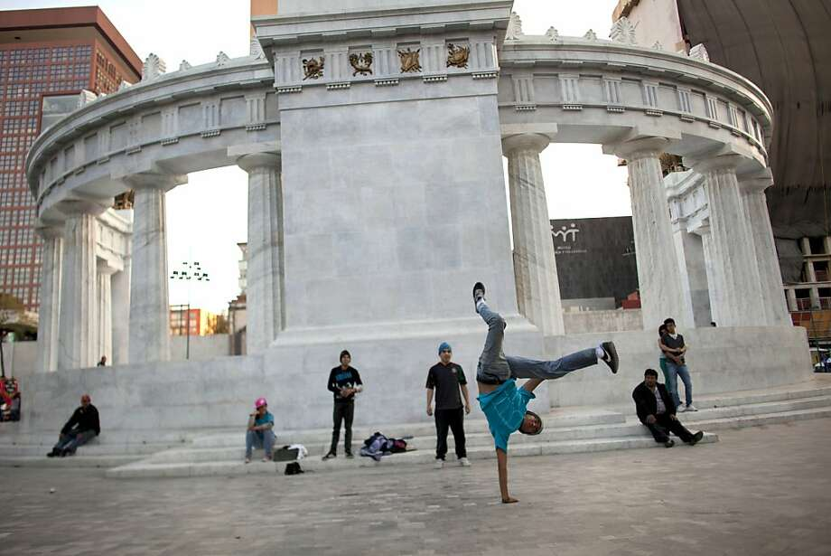 A dancer shows off his moves at Alameda Central, which is undergoing a major makeover that will attempt to transform the gritty plaza into Mexico City's version of Times Square. Photo: Alexandre Meneghini, Associated Press