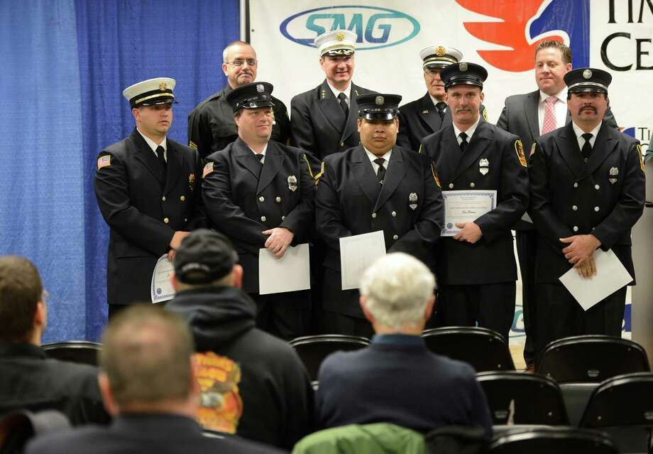 Albany County Executive Dan McCoy, far right in background acknowledges the work done by Albany County firefighters that volunteers to work on Long Island during the Super Storm Sandy First Responder Recognition Program held at the Times Union Center in Albany, N.Y.  Dec 27, 2012. (Skip Dickstein/Times Union) Photo: SKIP DICKSTEIN / 00020583A