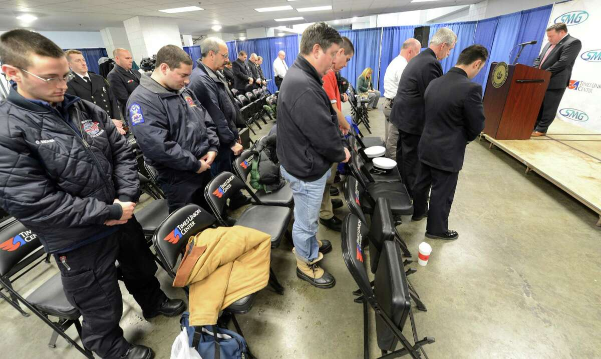 Firefighters from across Albany County bow their heads in memory of the two firefighters killed in the Webster, N.Y. shootings during the Super Storm Sandy First Responder Recognition Program held at the Times Union Center in Albany, N.Y. Dec 27, 2012. (Skip Dickstein/Times Union)