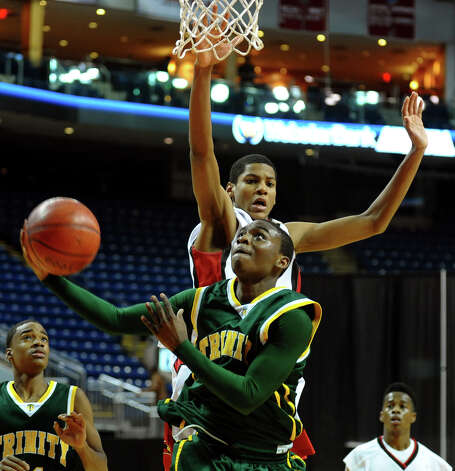 Trinity Catholic's #2 Schadrac Casimir goes up to the basket as LaSalle Academy's #3 Emmanuel McNeil defends, during Northeast Christmas Classic basketball tournament at the Webster Bank Arena in Bridgeport, Conn. on Thursday December 27, 2012. Photo: Christian Abraham / Connecticut Post