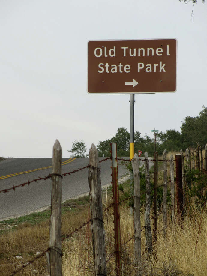 The state park sign for the Old Tunnel State Park is on Old San Antonio Road between Comfort and Fredericksburg.