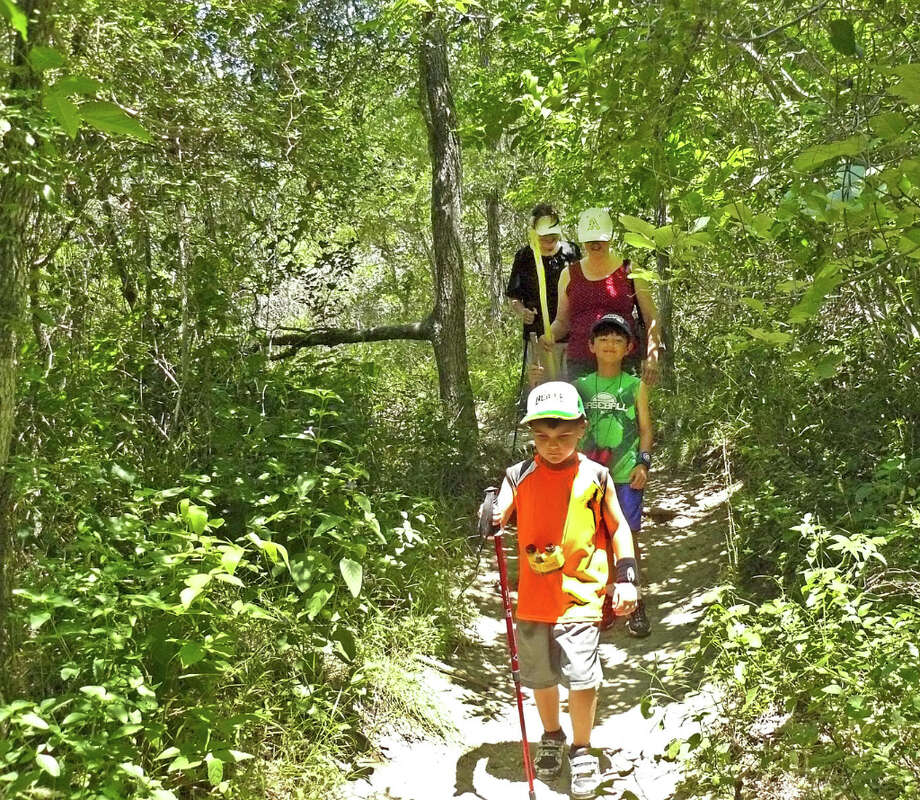 A family hikes at McKinney Falls State Park on National Trails Day.