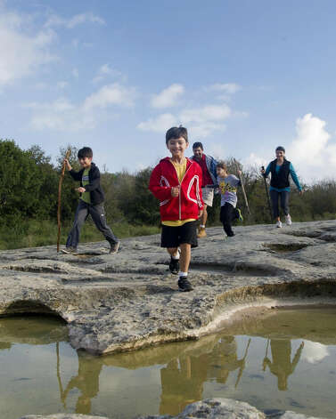 A family hikes at McKinney Falls State Park. (Chase Fountain, TPWD / Courtesy Photo)