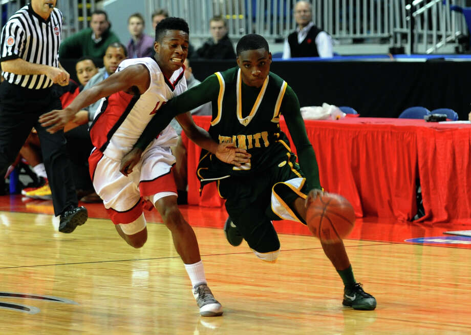 Trinity Catholic's #2 Schadrac Casimir breaks past LaSalle Academy's #10 Dwayne Pow, during Northeast Christmas Classic basketball tournament at the Webster Bank Arena in Bridgeport, Conn. on Thursday December 27, 2012. Photo: Christian Abraham