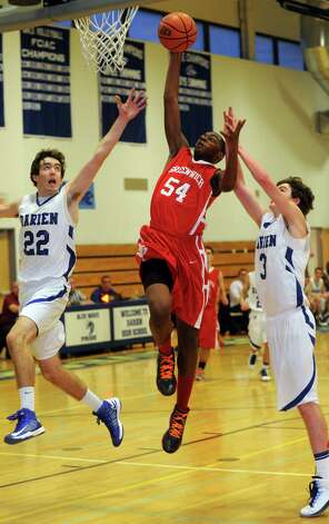 Greenwich's Leonel Hyatt takes a shot as he is defended by Darien's Henry Baldwin, left, and George Phillips, right, during the Tony LaVista Tournament on Thursday, December 27, 2012, at Darien High School. Photo: Lindsay Niegelberg, Niegelberg / Stamford Advocate