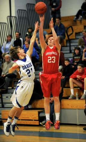 Greenwich's Jake Tennebaum takes a shot as he is defended by Darien's Matt Staubi during the Tony LaVista Tournament on Thursday, December 27, 2012, at Darien High School. Photo: Lindsay Niegelberg, Niegelberg / Stamford Advocate