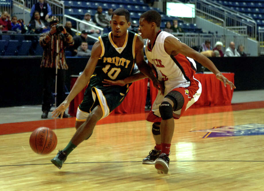 Trinity Catholic's #10 Neno Merritt drives to the basket as LaSalle Academy's #21 Raheem James defends, during Northeast Christmas Classic basketball tournament at the Webster Bank Arena in Bridgeport, Conn. on Thursday December 27, 2012. Photo: Christian Abraham