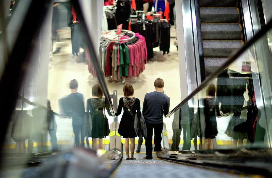 In this  Wednesday, Dec. 12, 2012, photo, a couple descend an escalator while shopping at an H& M store, in Atlanta.  U.S. consumer confidence tumbled in December, driven lower by fears of sharp tax increases and government spending cuts set to take effect next week. The Conference Board said Thursday that its consumer confidence index fell this month to 65.1, down from 71.5 in November. That's second straight decline and the lowest level since August.  (AP Photo/David Goldman) Photo: David Goldman