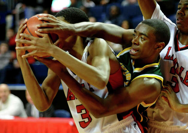 Trinity Catholic's #5 Brandon Wheeler, right, tries to steal a rebound away from LaSalle Academy's #3 Emmanuel McNeil, during Northeast Christmas Classic basketball tournament at the Webster Bank Arena in Bridgeport, Conn. on Thursday December 27, 2012. Photo: Christian Abraham
