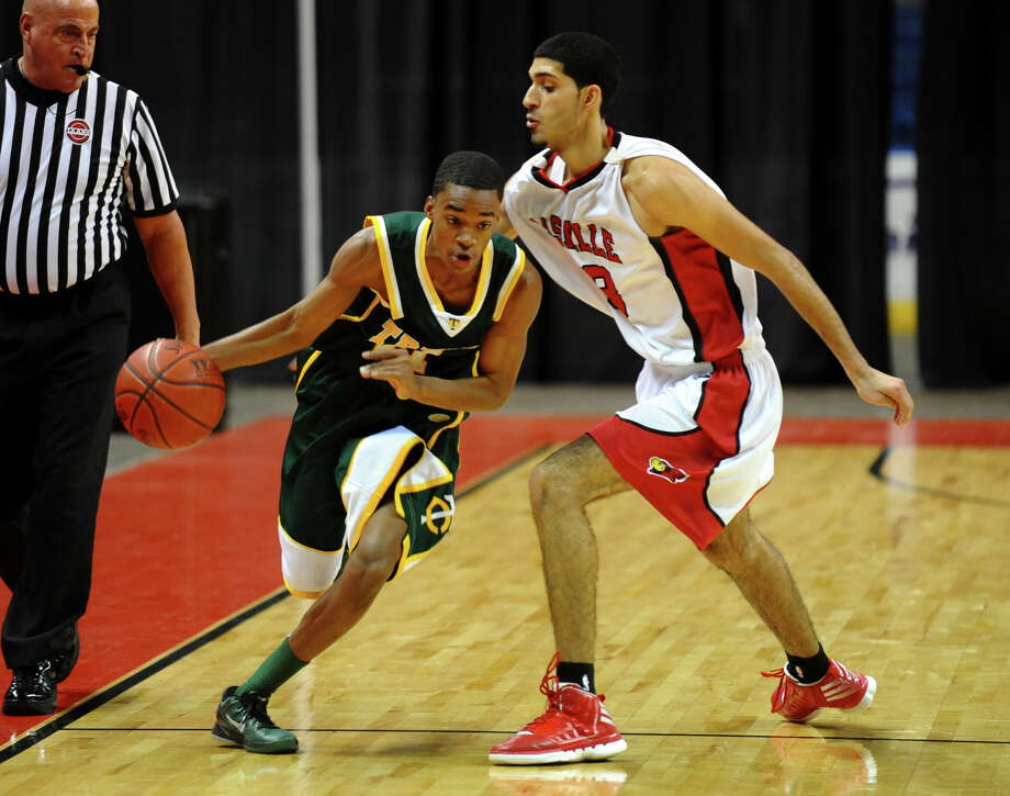 Trinity Catholic's #11 Justice Page drives the ball past LaSalle Academy's #23 Chris Polanco, during Northeast Christmas Classic basketball tournament at the Webster Bank Arena in Bridgeport, Conn. on Thursday December 27, 2012. Photo: Christian Abraham