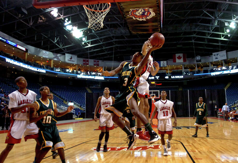 Trinity Catholic's #3 Tremaine Fraiser is fouled by LaSalle Academy's #23 Chris Polanco as he attempts a basket, during Northeast Christmas Classic basketball tournament at the Webster Bank Arena in Bridgeport, Conn. on Thursday December 27, 2012. Photo: Christian Abraham