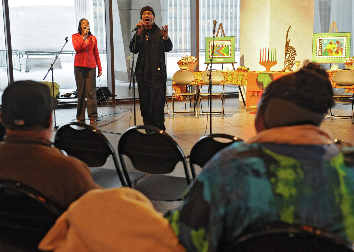 Betty Harper of Schenectady and Freddy Ingleton of Albany sing a song to test the sound system at the Annual Capital Kwanzaa event at the New York State Museum on Thursday Dec. 27, 2012 in Albany, N.Y. (Lori Van Buren / Times Union)