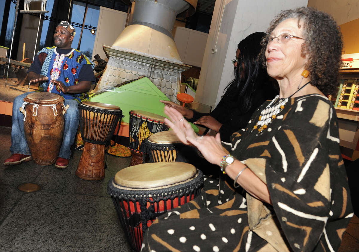 Zorkie Nelson, left, leads a drumming circle including Miki Conn, right, at the Annual Capital Kwanzaa event at the New York State Museum on Thursday Dec. 27, 2012 in Albany, N.Y. (Lori Van Buren / Times Union)