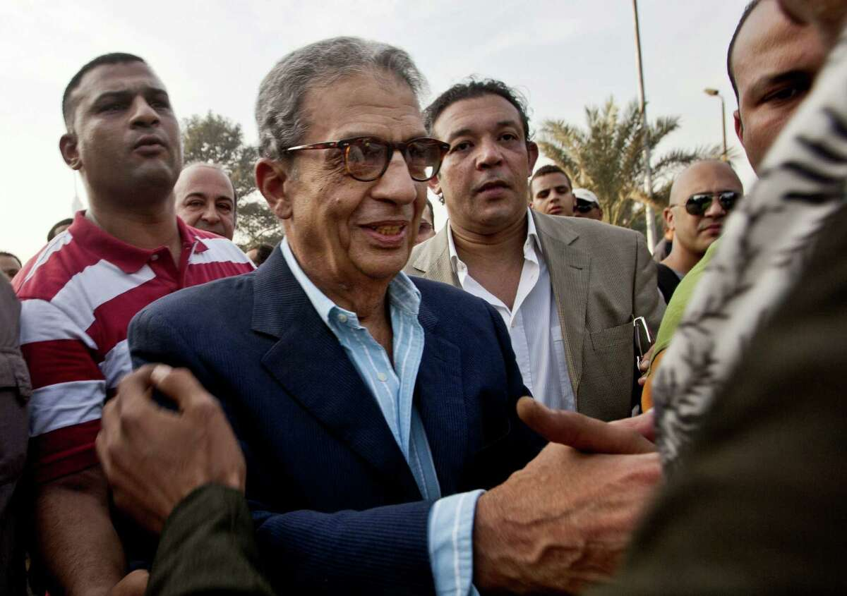 FILE - In this Friday, Nov. 30, 2012 file photo, former foreign minister and presidential candidate Amr Moussa, center, greets supporters as he arrives to Tahrir Square to join other liberal and secular parties for a major protest against Egyptian President Mohammed Morsi's latest decrees granting himself almost complete powers and allowing a rushed constitution to be presented for a vote. An Egyptian official says the country?'s top prosecutor has ordered an investigation into accusations against opposition leaders, Mohammed ElBaradei, Amr Moussa, and Hamdeen Sabahi, of incitement to overthrow the regime. (AP Photo/Thomas Hartwell, File)