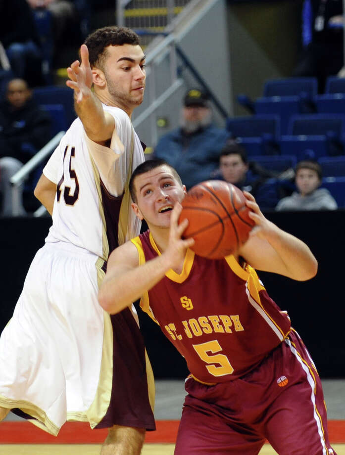 St. Joseph's #5 Jonathan Dzurenda gets pressure from Monsignor Farrell's #15 Damian Murphy as he attempts a shot, during Northeast Christmas Classic basketball tournament at the Webster Bank Arena in Bridgeport, Conn. on Thursday December 27, 2012. Photo: Christian Abraham / Connecticut Post
