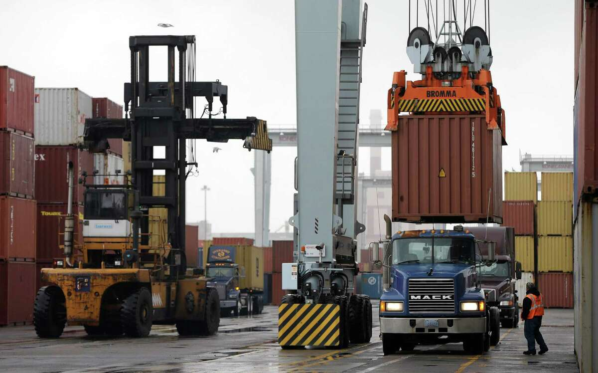 FILE - In this Dec. 18, 2012 file photo, a truck driver watches as a freight container, right, is lowered onto a tractor trailer by a container crane at the Port of Boston in Boston. The crane and a reach stacker, left, are operated by longshoremen at the port. The longshoremen's union may strike if they are unable to reach an agreement on their contract, which expires Dec. 29, 2012. A walkout by dock workers represented by the International Longshoremen?'s Association would bring commerce to a near halt at ports from Boston to Houston. (AP Photo/Steven Senne, File)