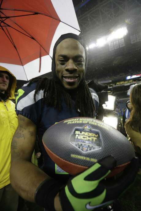 "Seattle Seahawks' Richard Sherman shows off his ""Sunday Night Football Player of the Game"" ball after the team beat the San Francisco 49ers in an NFL football game, Sunday, Dec. 23, 2012, in Seattle. The Seahawks won 42-13. (AP Photo/Elaine Thompson) Photo: Elaine Thompson, STF / AP"