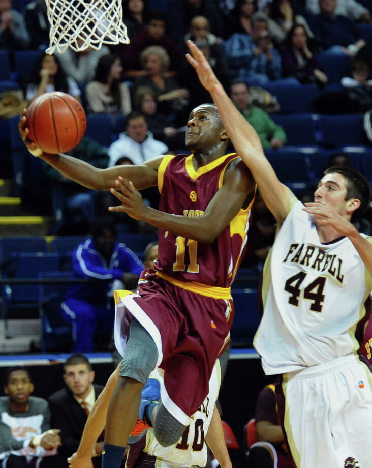 St. Joseph's #11 Quincy McKnight lays up the ball as Monsignor Farrell's #44 Thomas Vazzana defends, during Northeast Christmas Classic basketball tournament at the Webster Bank Arena in Bridgeport, Conn. on Thursday December 27, 2012. Photo: Christian Abraham / Connecticut Post