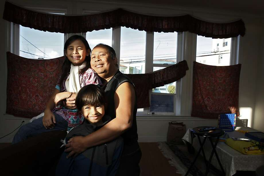 Arthur Caberto, right, with his kids Gemma, 8, left, and Anthony, 7, bottom, in their San Francisco, Calif., apartment on Thursday, December 27, 2012. Caberto was able to get two beds for his children through the Chronicle's Season of Sharing Fund. Photo: Carlos Avila Gonzalez, The Chronicle